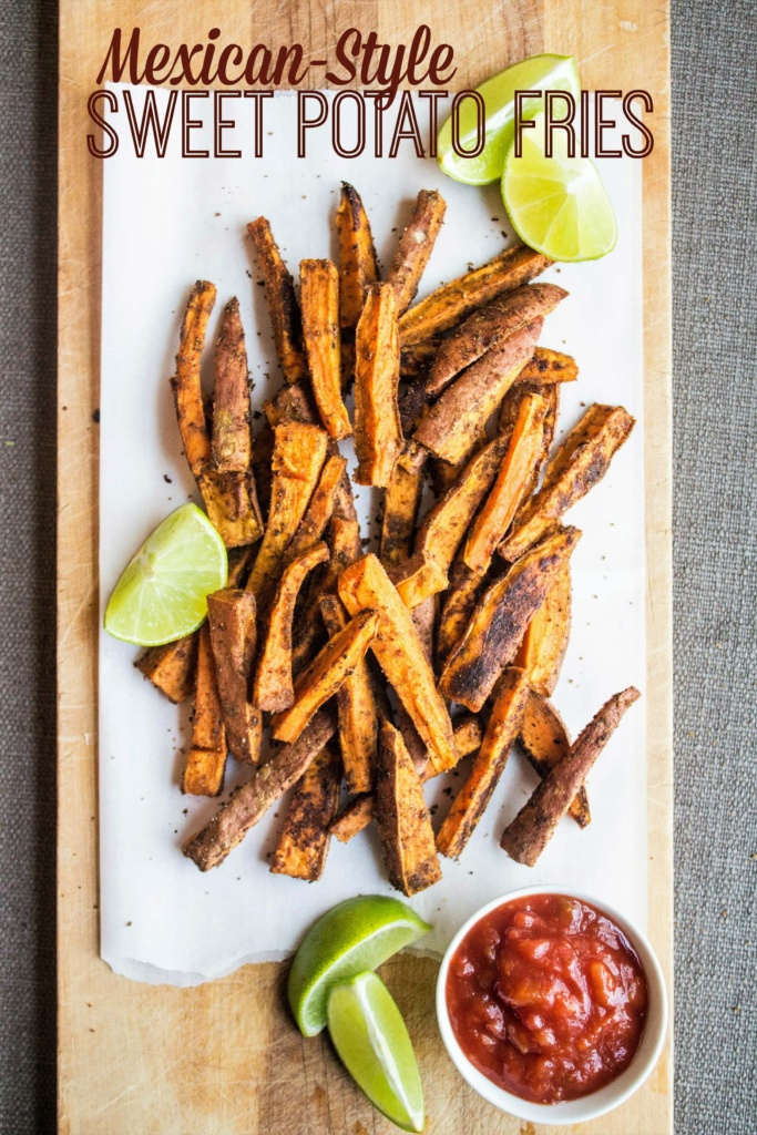 seasoned sweet potato fries on a wooden platter with lime slices and salsa