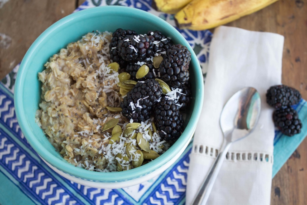 bowl of oatmeal with blackberries, bananas, and nuts