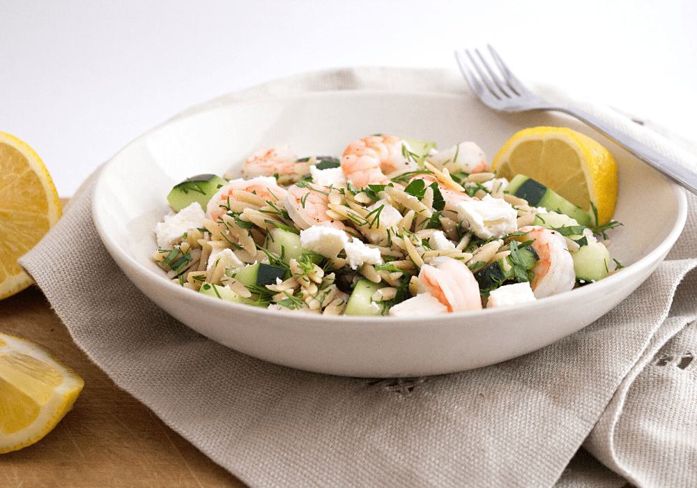 greek pasta salad with shrimp and feta in a white bowl with lemon slices