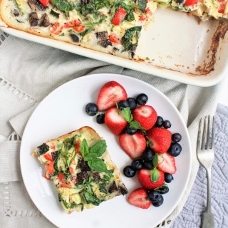 smoked salmon and veggie egg casserole in a dish with a slice cut out, served with fruit