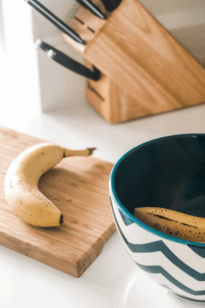 banana on cutting board with fruit bowl