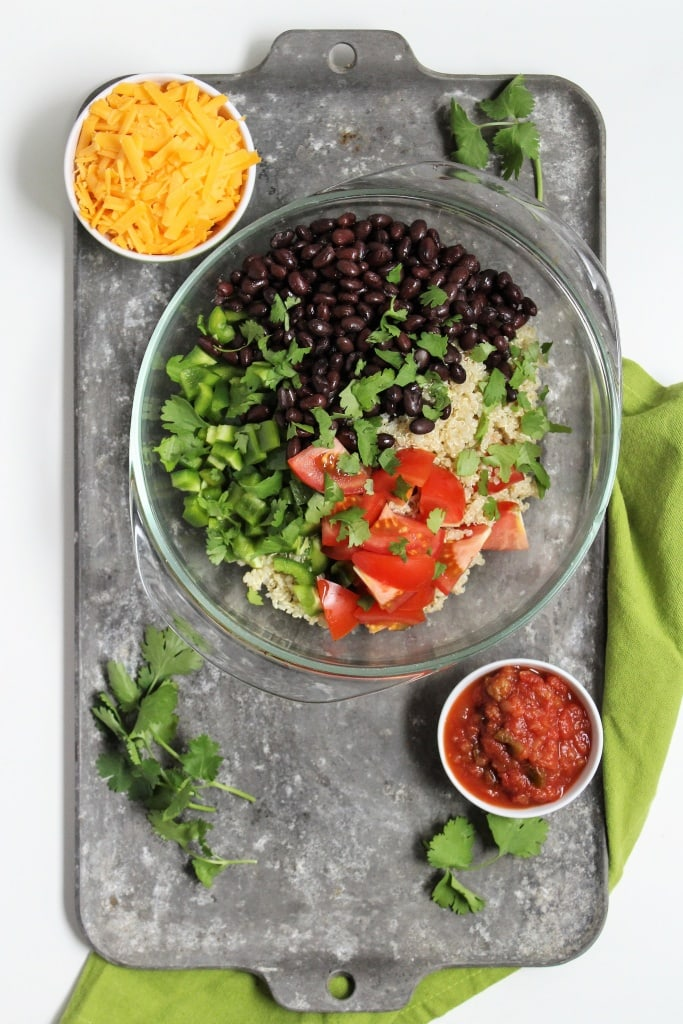 bowl with black beans, shredded cheese, salsa, bell peppers, quinoa, and cilantro