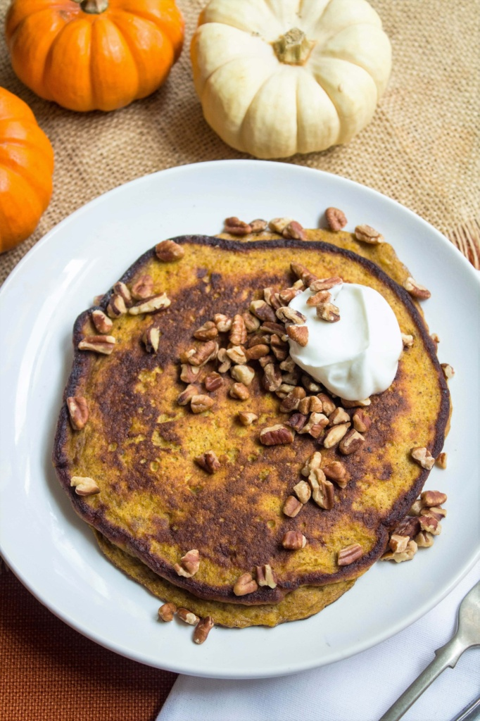 pumpkin pancakes with pecans and yogurt on top with mini pumpkins next to the plate