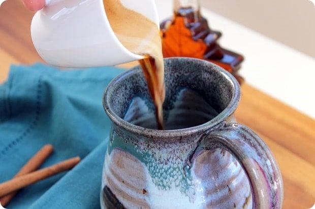 pouring espresso into a large ceramic mug