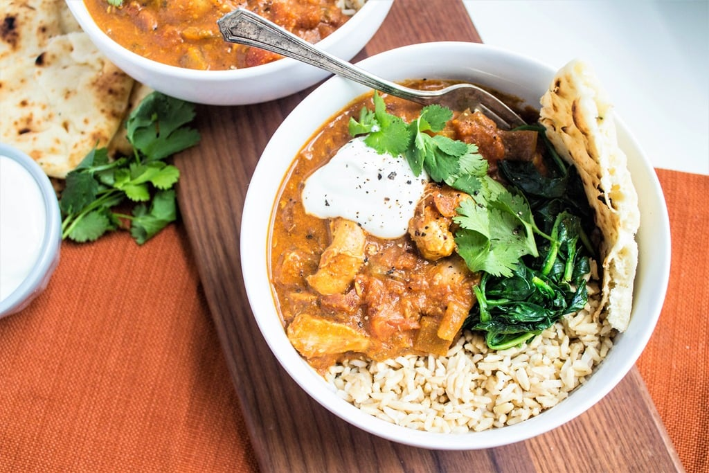 slow cooker chicken tikka masala with rice and pita bread in a bowl