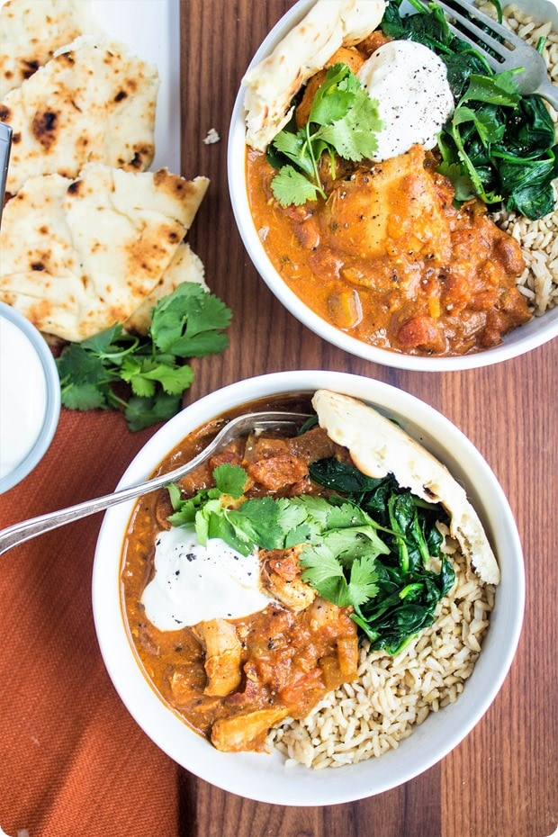 slow cooker chicken tikka masala in white bowls with naan bread