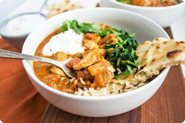 chicken tikka masala in a bowl with rice and spinach