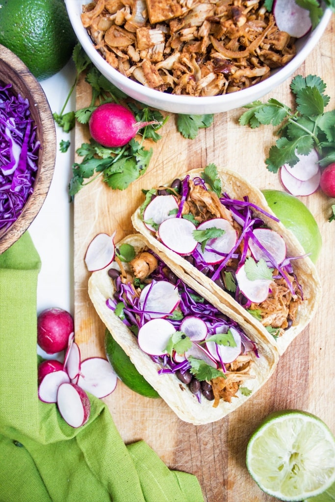 jackfruit tacos on a wooden platter with purple cabbage and radishes