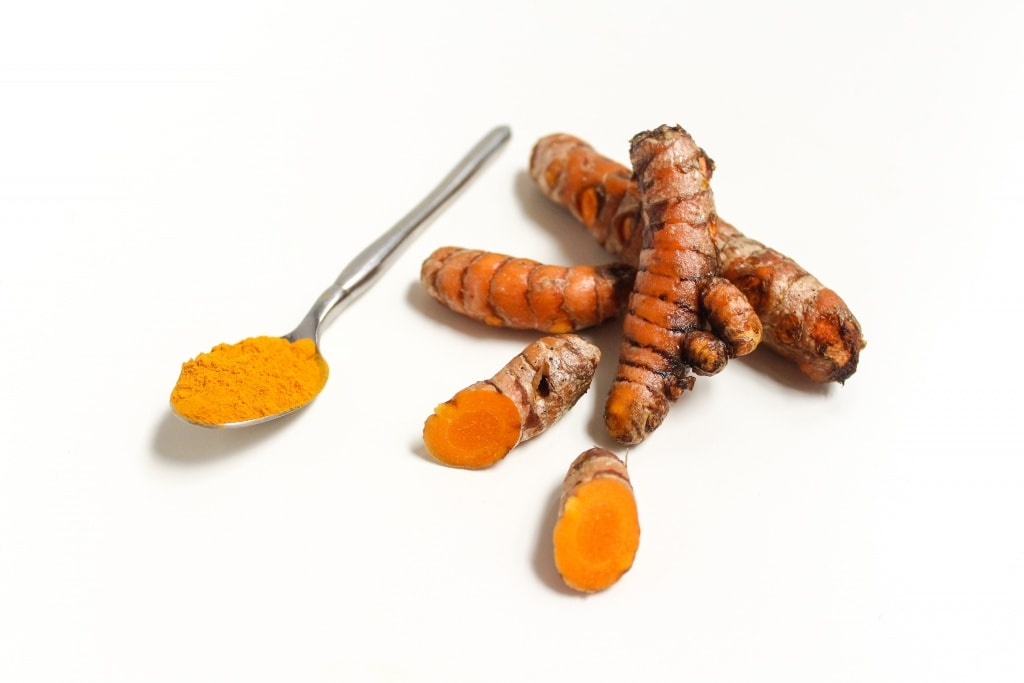 fresh ground turmeric in a spoon