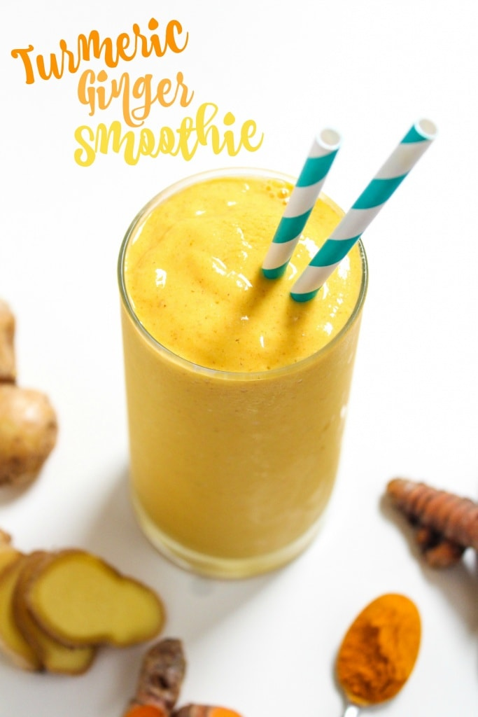 Ginger turmeric smoothie recipe with mango and pineapple in a glass cup with striped straws