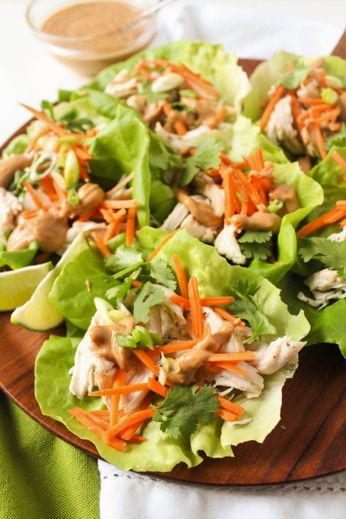 close up of chicken lettuce wraps on a wooden platter