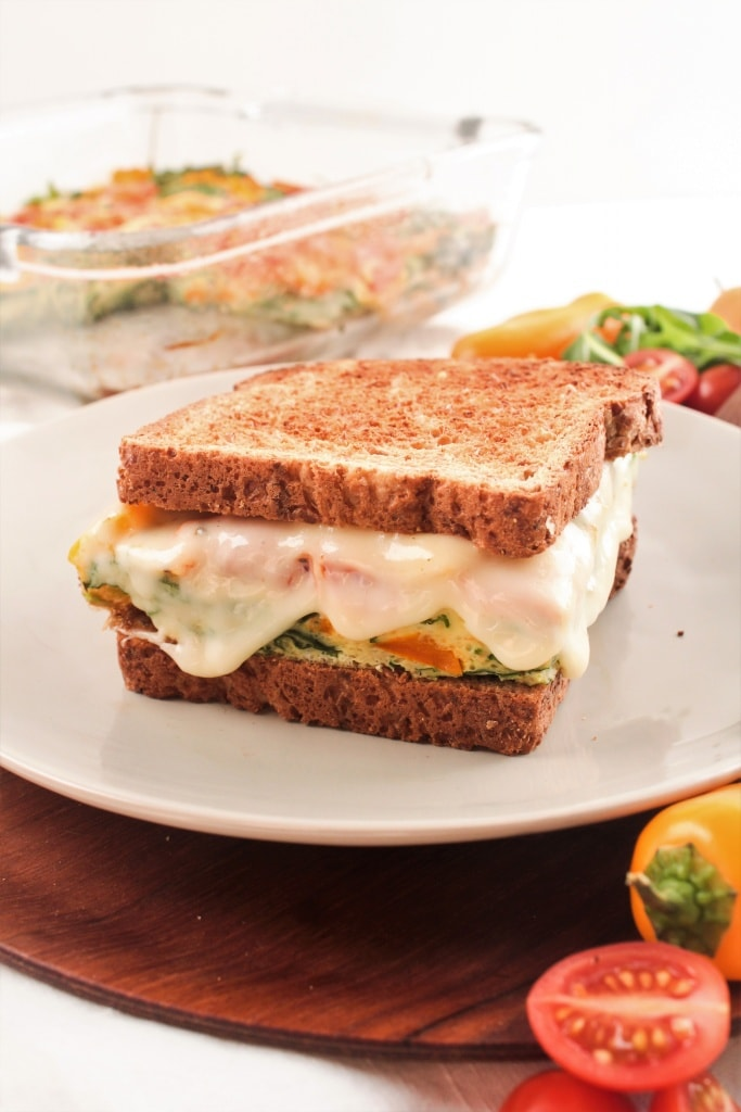 cheesy and veggie-packed breakfast sandwich on a plate