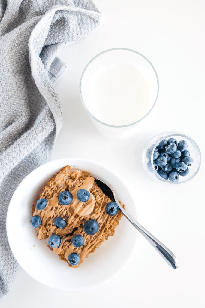 oatmeal in a white bowl with blueberries in a small jar