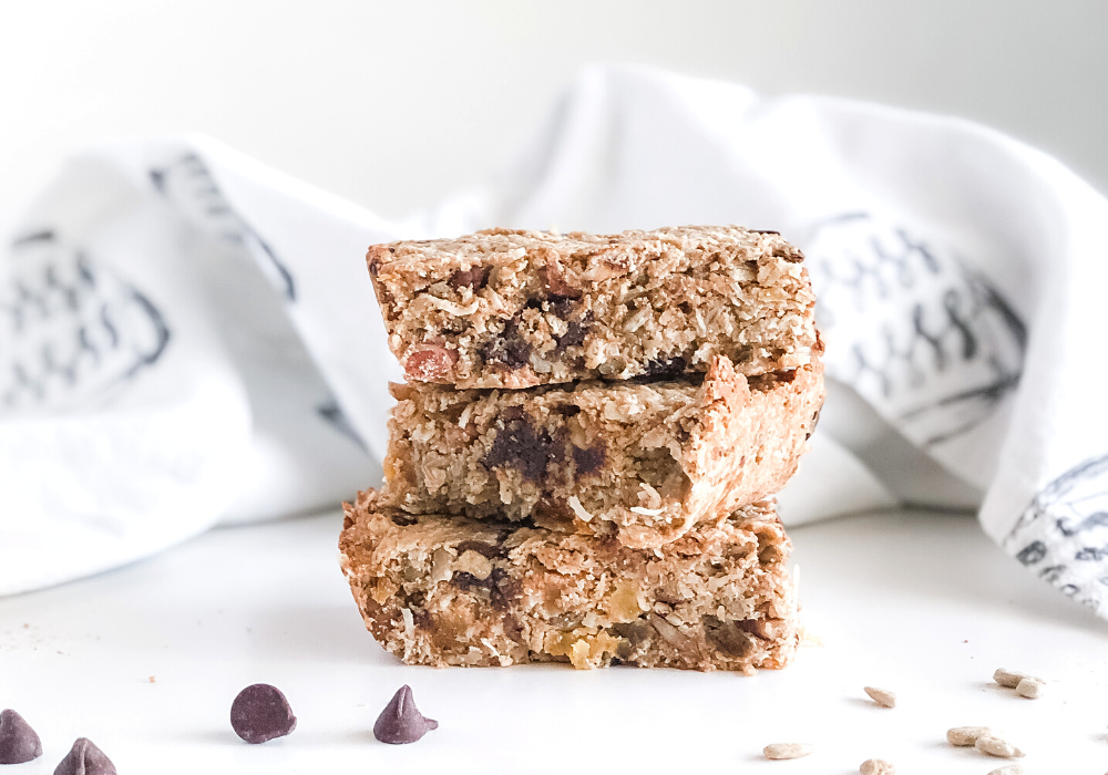granola bars stacked with chocolate chips and sunflower seeds scattered in front and a kitchen towel behind