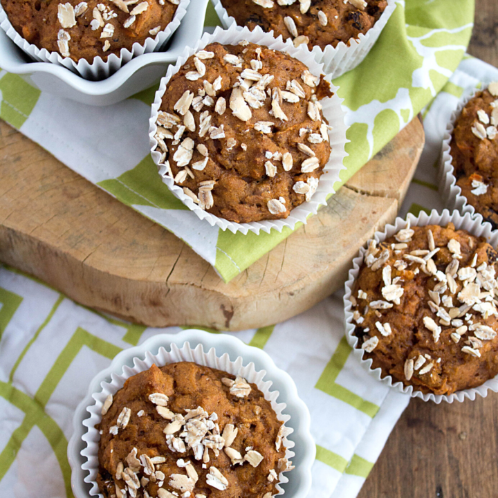 carrot cake muffins in a white and green kitchen towel