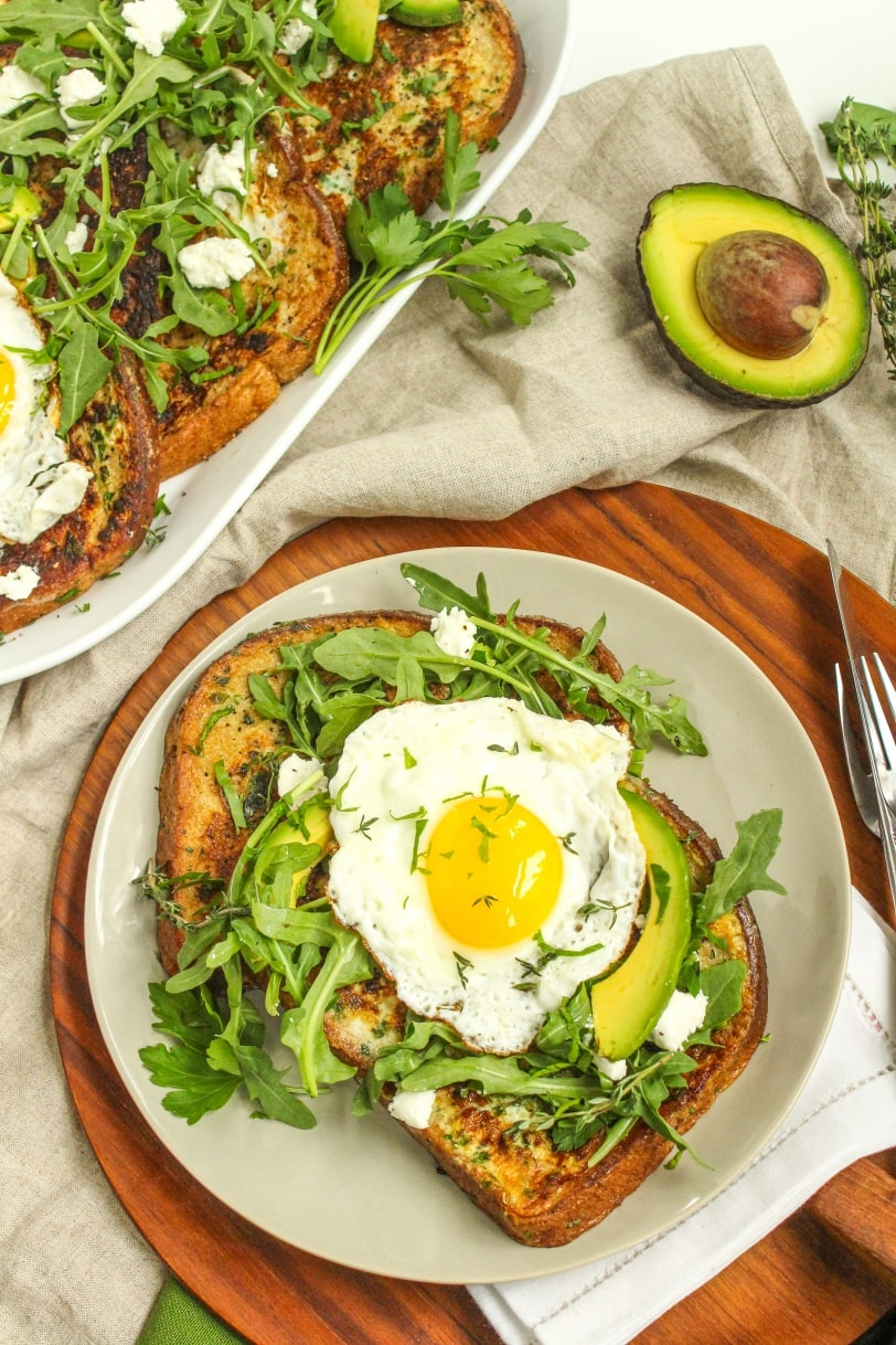 french toast with arugula, avocado, and fried eggs on top