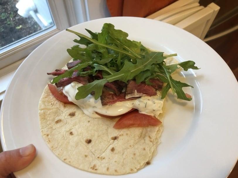 wrap with steak, tzatziki, tomato, arugula