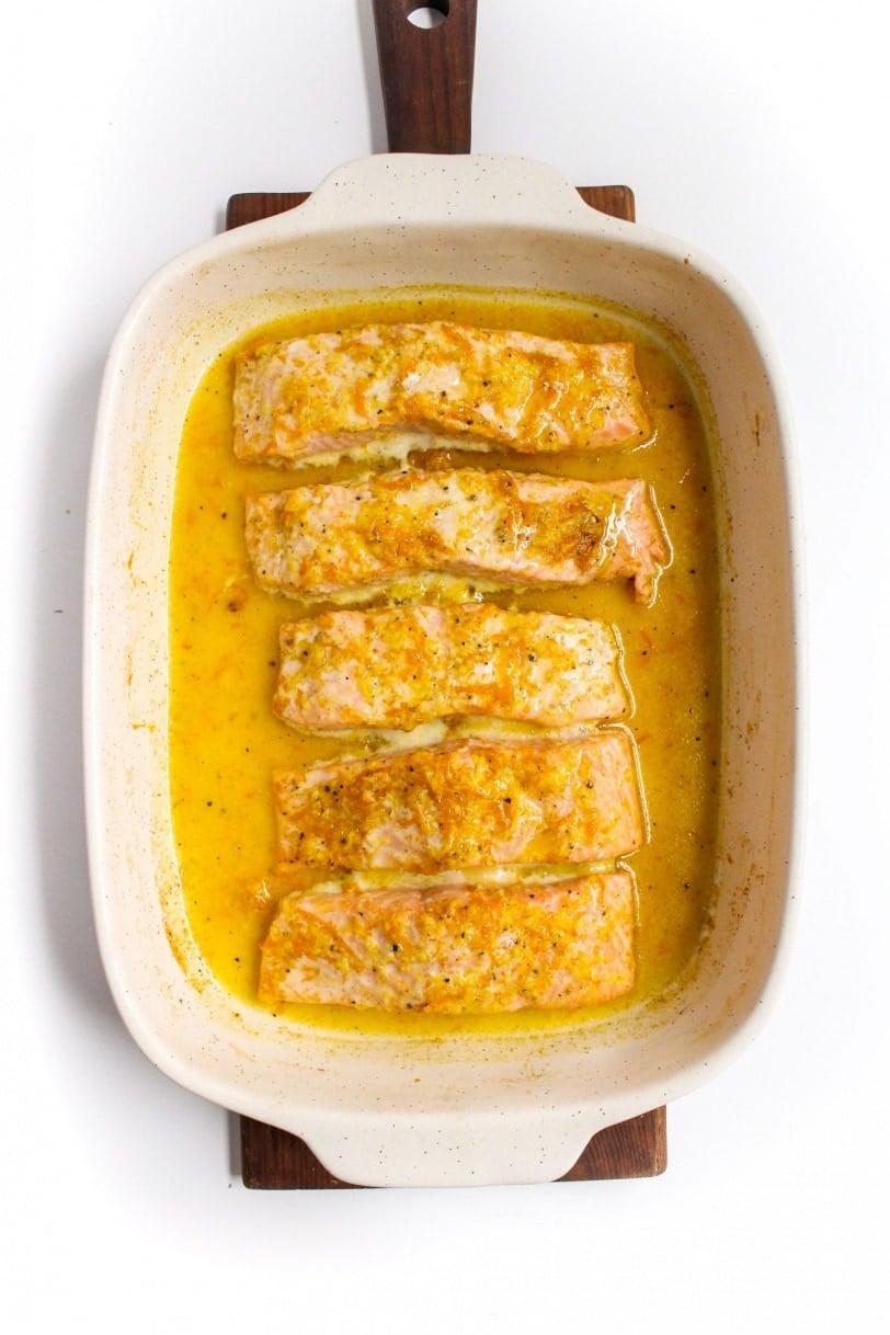 honey orange glaze marinated salmon in a white baking dish