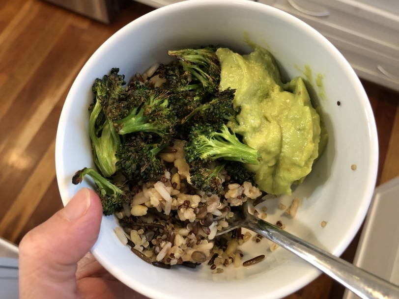 grain bowl with rice, lentils, roasted broccoli, and guacamole