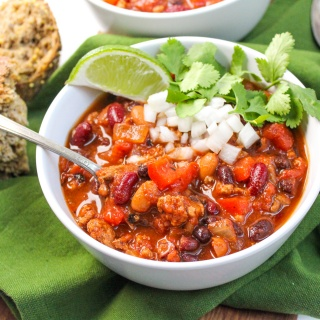 healthy slow cooker turkey chili in a white bowl with a lime, onions, and cilantro