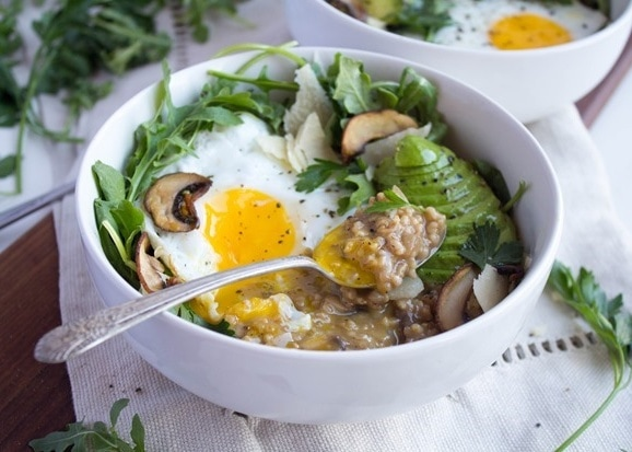 savory oatmeal with egg in a bowl with mushrooms and avocado