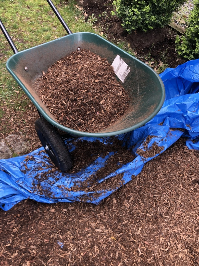 filling outdoor playhouse border with mulch