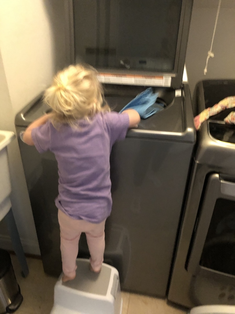 toddler helping with laundry