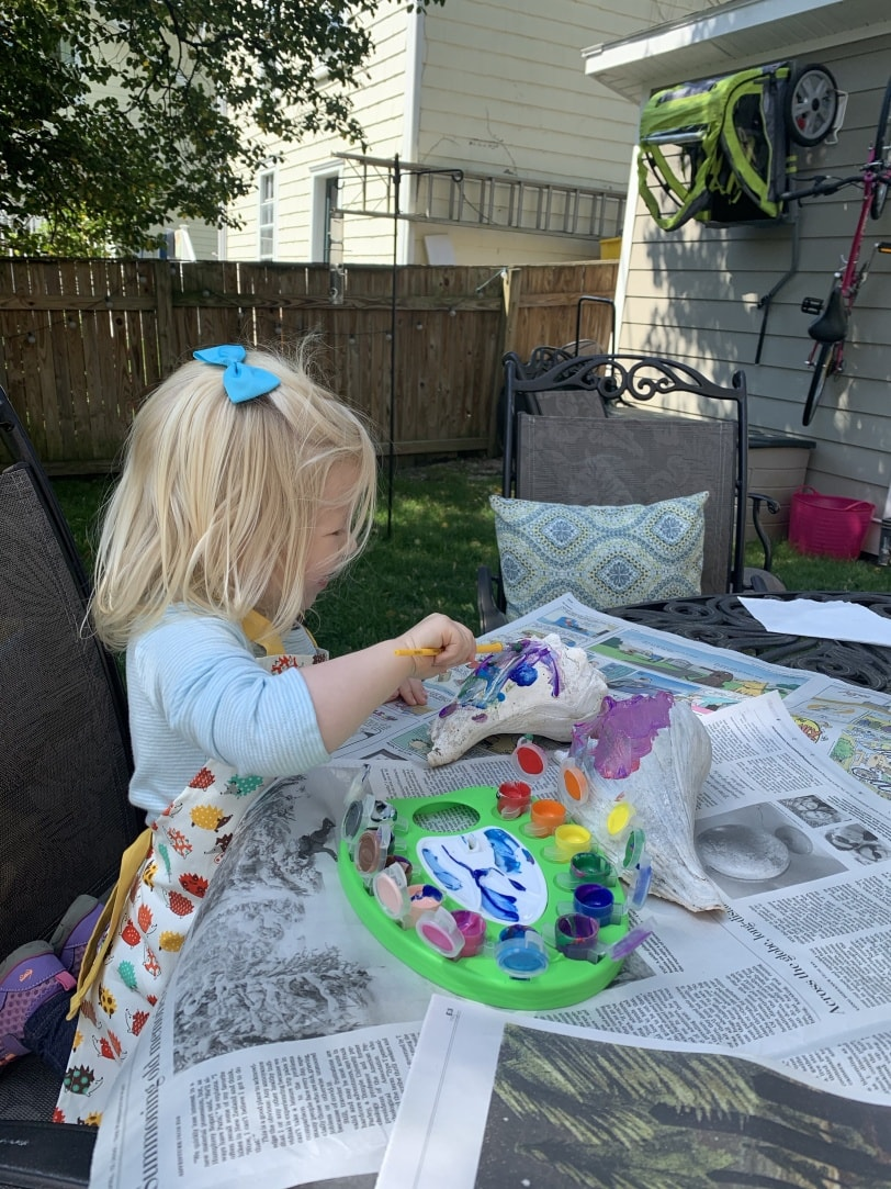 toddler painting a shell