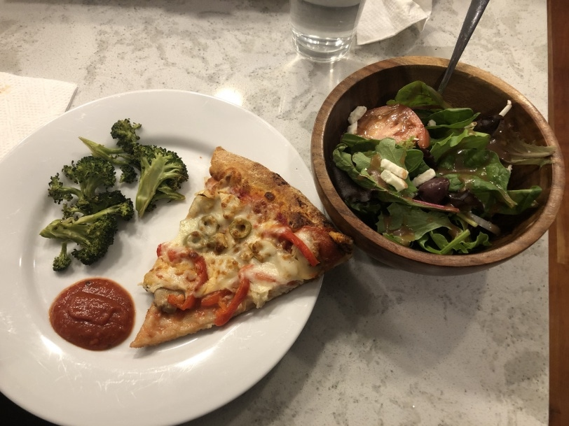 pizza with roasted broccoli and greek salad