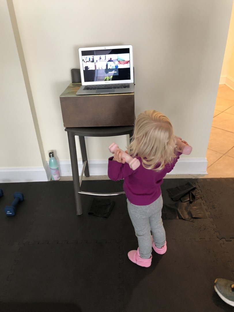 toddler holding weights and watching workout video