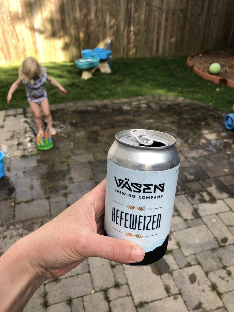 beer can with a toddler playing in a sprinkler in background