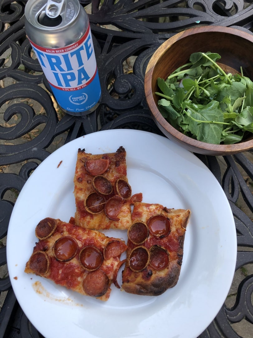 pepperoni pizza from andys pizza with a side salad and a trite IPA beer