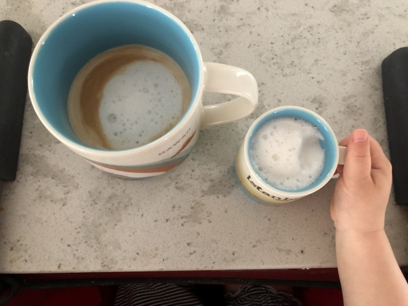 a large coffee cup holding a latte and a small espresso cup holding frothed milk