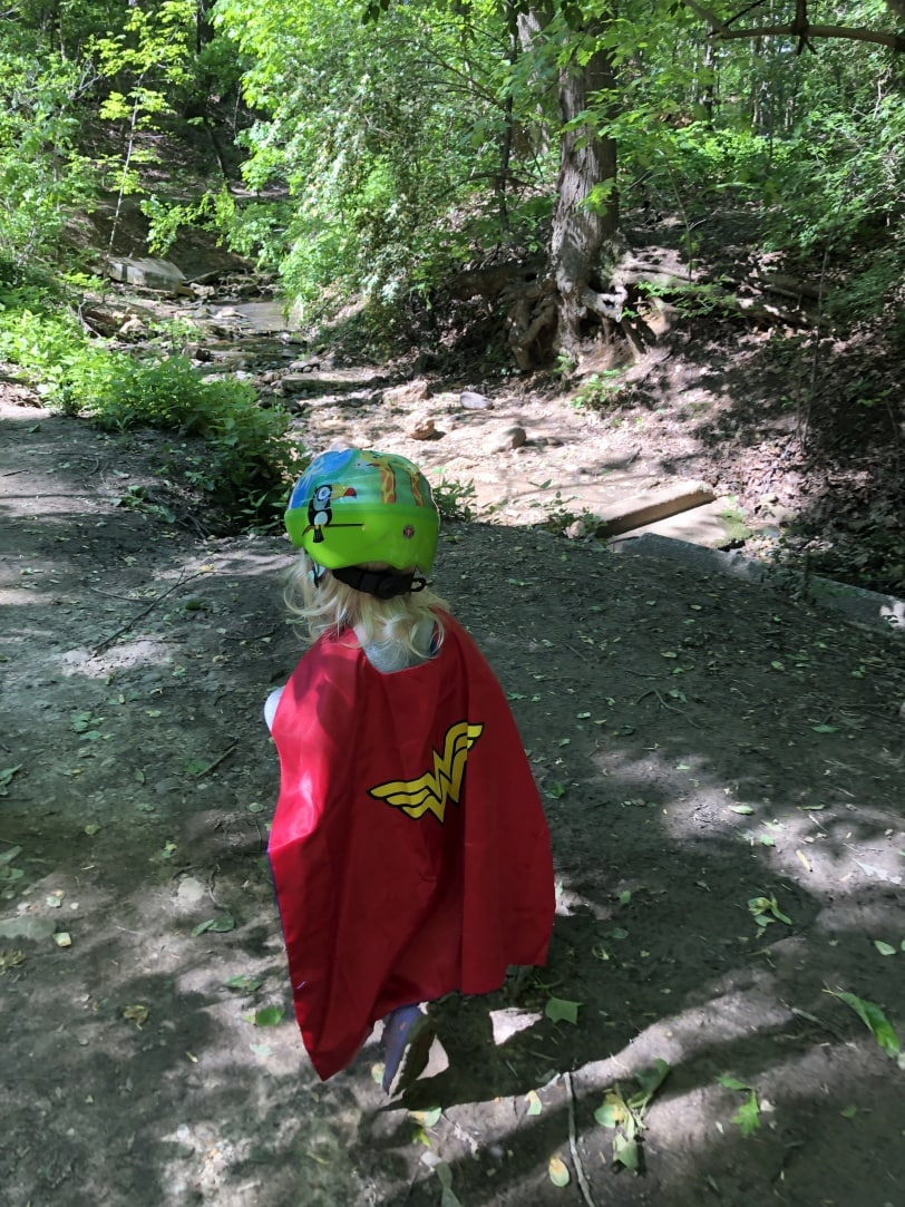 toddler hiking wearing a cape and helmet