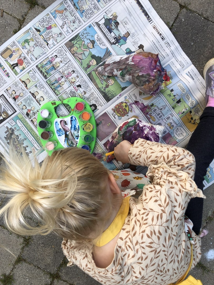 toddler painting a shell with watercolor paint