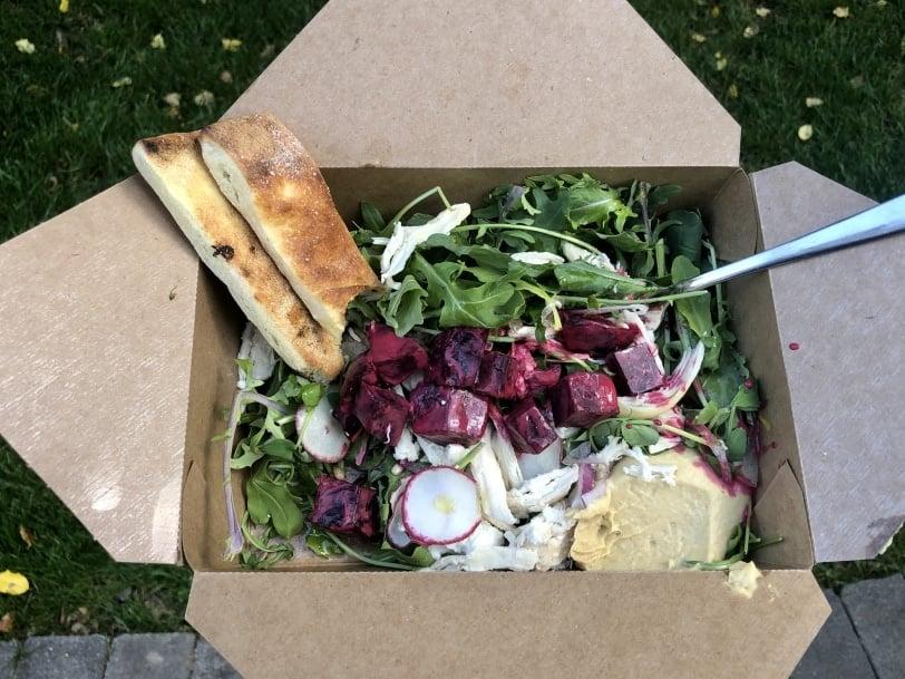 arugula salad with beets, radish, cheese, hummus, and bread