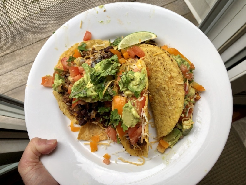 hard shell tacos with ground beef, black beans, cheese, tomato, yellow pepper, and avocado