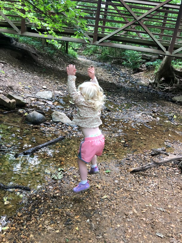 toddler throwing rocks into a stream