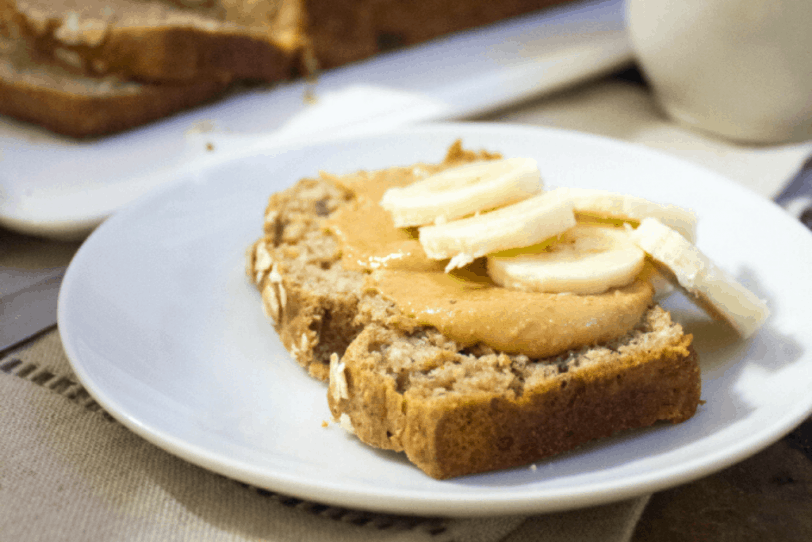 slice of whole wheat peanut butter banana bread (made with overripe bananas) on a white plate