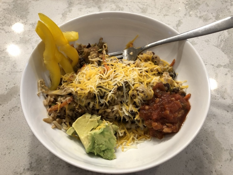 leftover mexican topped with cheese, salsa, avocado, and peppers