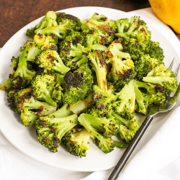 roasted broccoli on a plate with lemons