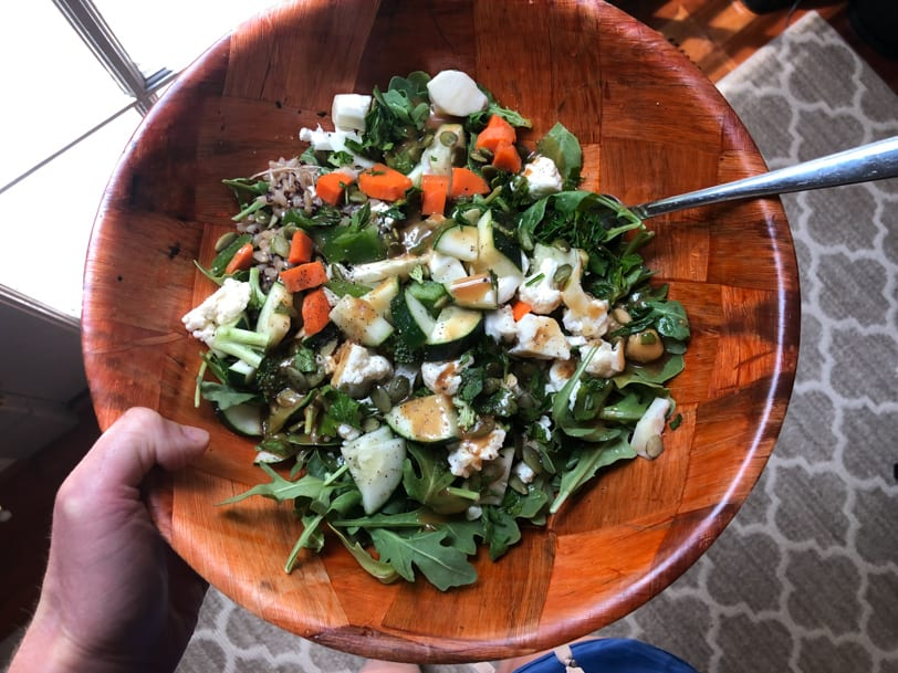 grain salad bowl with rice, feta, chickpeas, pumpkin seeds, cucumber, carrots, and balsamic vinaigrette