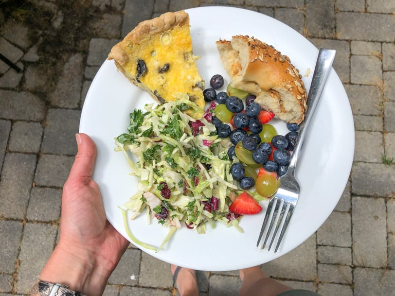 quiche, slaw salad, fruit, and bagel