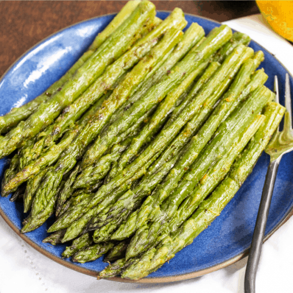 roasted asparagus on a white plate with lemons