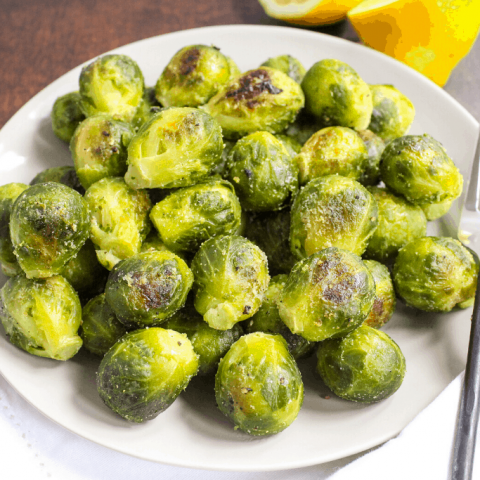 roasted brussels sprouts on a white plate with lemons