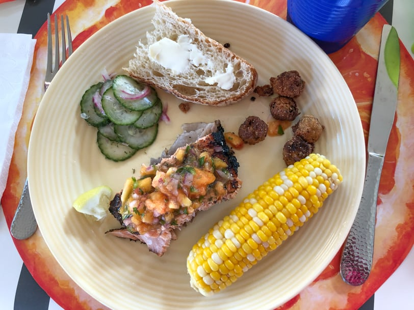 grilled salmon with corn, cucumber salad, and bread