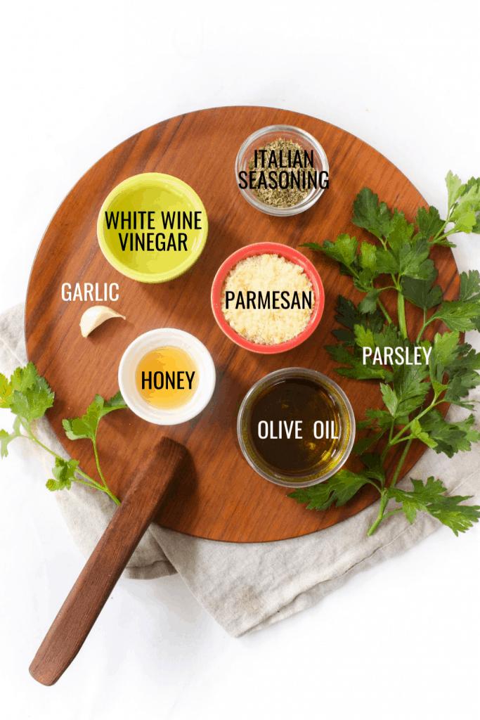 creamy Italian dressing ingredients on a wooden platter
