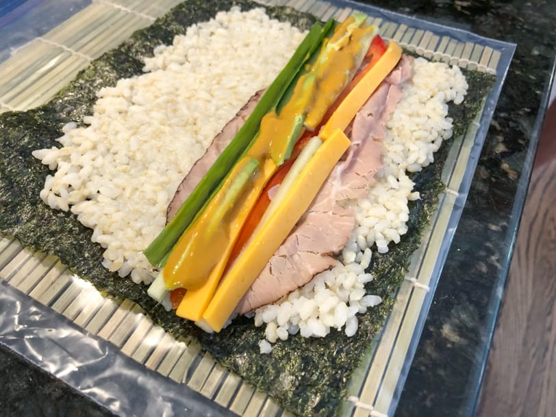 sushi with roast beef, avocado, cucumber, cheddar cheese, red pepper, and mustard soy sauce