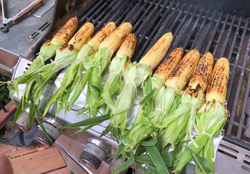 corn on the grill with the husks flipped up
