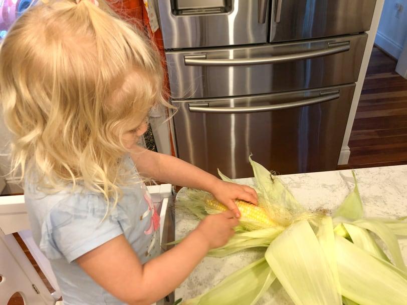 toddler shucking corn